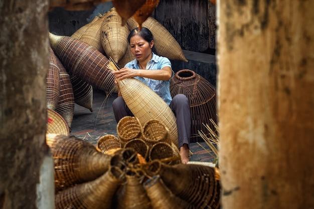 Alter vietnamesischer weiblicher handwerker, der die traditionelle bambusfischfalle macht