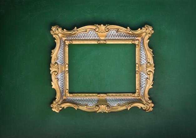 Alter viktorianischer vergoldeter zierrahmen an einer grünen wand barock-rokoko der renaissance