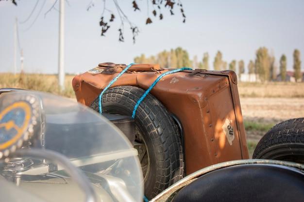 Alter vintage-lederkoffer, befestigt an einem alten oldtimer-italiener, der bereit ist, eine neue reise zu unternehmen. abientazione: italienische landschaft.