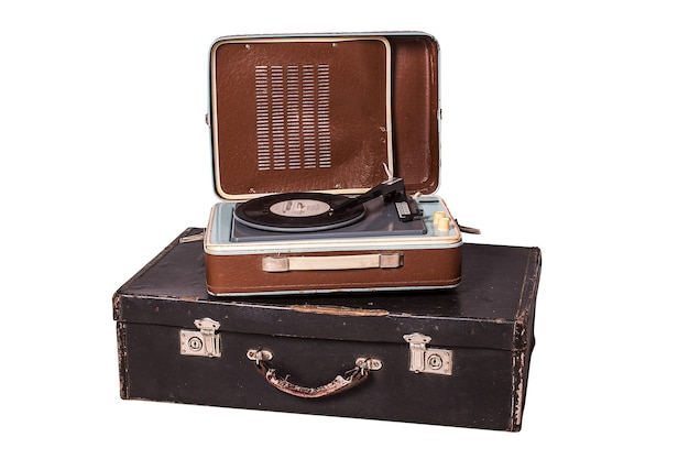 Alter vinyl-player auf einem alten koffer, auf einem weißen