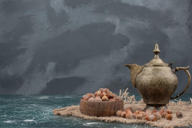 Alter wasserkocher mit hölzernem teller der nüsse auf marmor