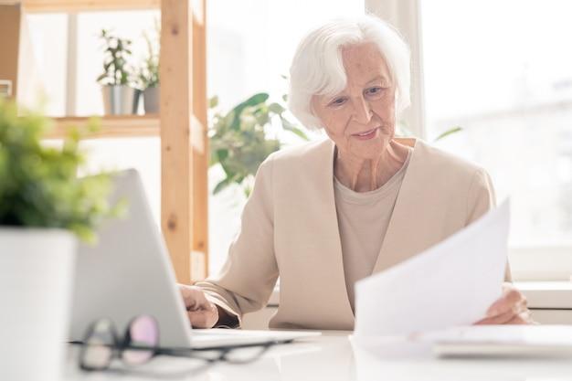 Alter weiblicher ökonom oder bankier, der durch finanzpapiere schaut, während er am schreibtisch vor laptop im büro sitzt