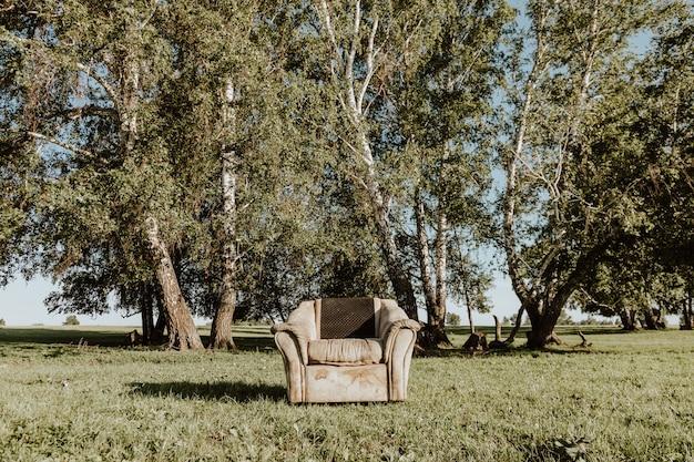 Alter weicher stuhl mit flecken steht mitten auf einer grünen wiese, im hintergrund ein wald an einem warmen sommertag. konzept der einsamkeit und selbstisolation in der natur