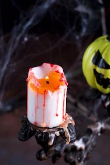 Alter weinlese-kerzenhalter mit brennender kerze auf einem gark-hintergrund mit gemaltem gelbem halloween-kürbis.
