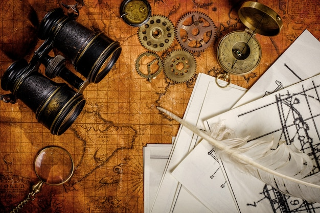 Alter weinlese-retrokompass und fernglas auf alter weltkarte