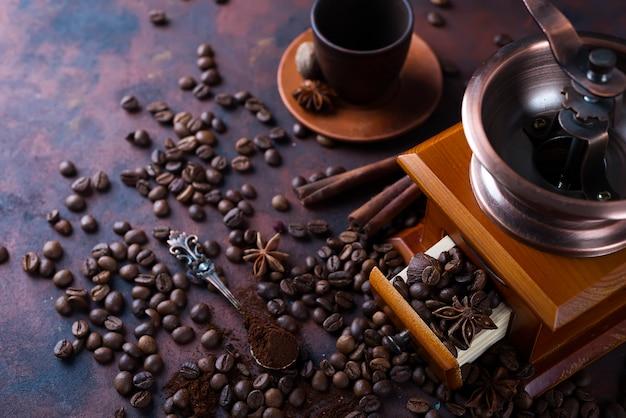 Alter weinleseschleifer mit röstkaffeebohnen und mahlkaffee auf steinhintergrund.