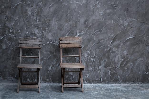 Alter weinlesestuhl aus holz bei dunkler betonwandbeschaffenheit
