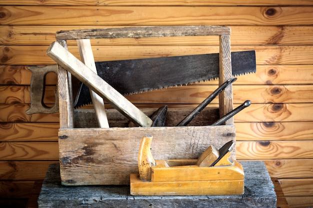 Alter weinlesewerkzeugkasten mit hämmern, säge, flugzeug und zangen in der zimmerei