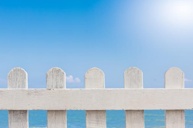 Alter weißer bretterzaun auf einem blauen himmel