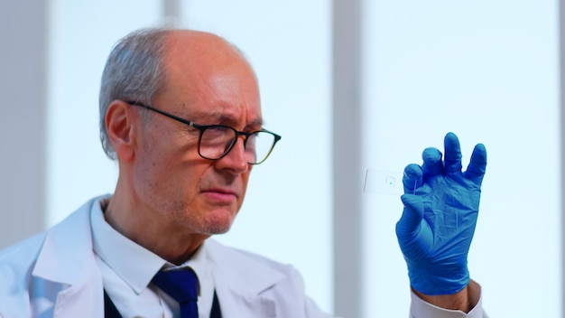 Alter wissenschaftlermann, der virusprobe in ausgerüstetem labor analysiert. wissenschaftler, der mit verschiedenen bakterien-, gewebe- und blutproben arbeitet, pharmazeutische forschung für antibiotika gegen coronavirus-pandemie