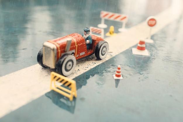Alter zinnspielzeug-modellrennfahrer im regen.
