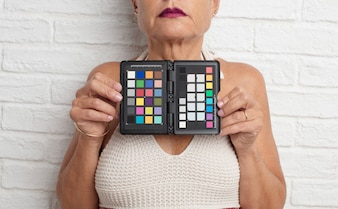 Ältere coole Frau mit einer grauen Karte gegen weiße Backsteinmauerrückseite
