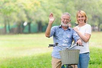 Ältere Paare, die ihr Fahrrad entlang glücklich glücklich sprechen gehen.