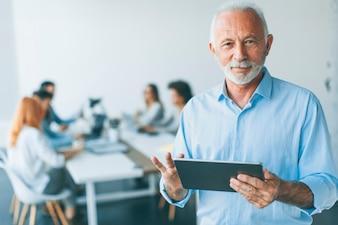 Älterer Geschäftsmann, der mit digitaler Tablette in seiner Hand steht