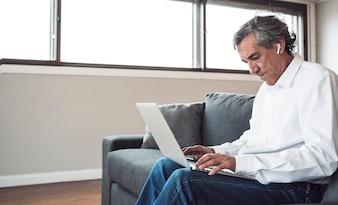Älterer Mann, der auf Sofa unter Verwendung des Laptops sitzt