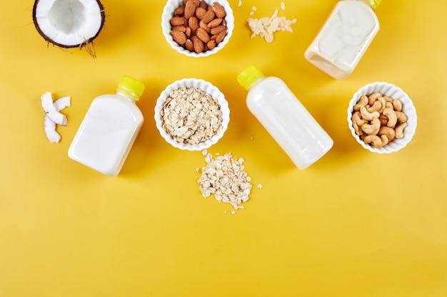 Alternative arten von veganer milch in flaschen auf gelbem grund