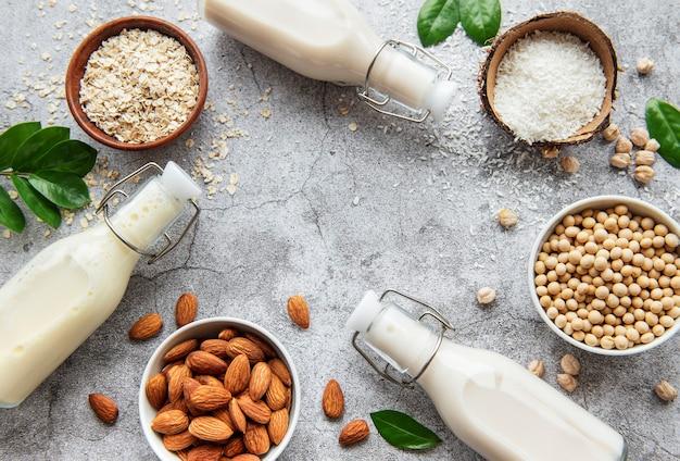 Alternative arten von veganer milch in glasflaschen auf einer betonoberfläche