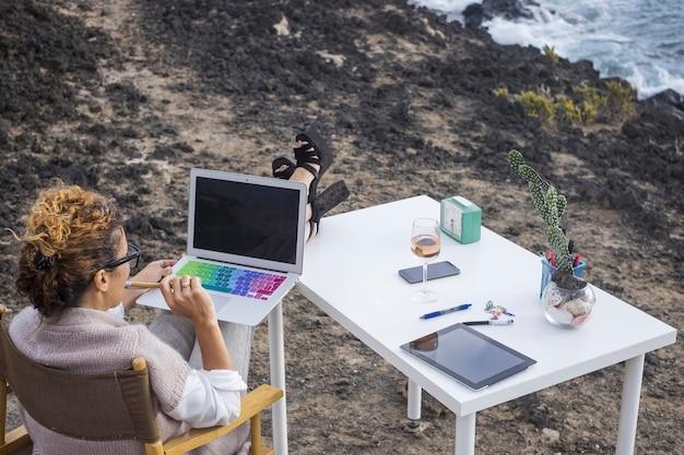 Alternativer bürostandort für elegante managerin, kaukasierin, die mit modernem laptop der technologie direkt vor dem ozean arbeitet