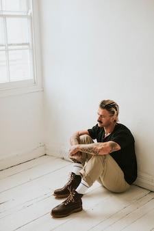 Alternativer mann, der auf einem weißen holzboden sitzt