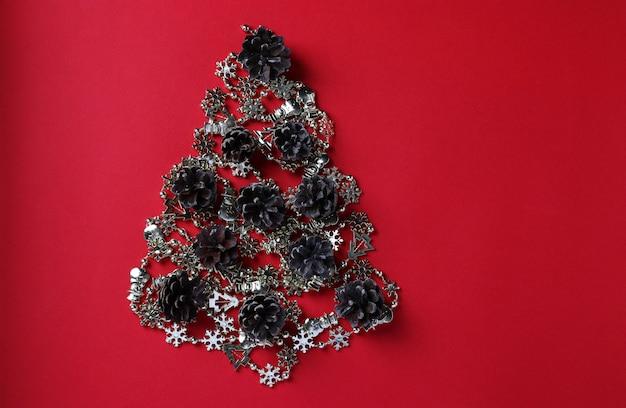 Alternativer weihnachtsbaum aus glänzender girlande und zapfen auf rot. platz für wünsche. sicht von oben. frohes neues jahr.
