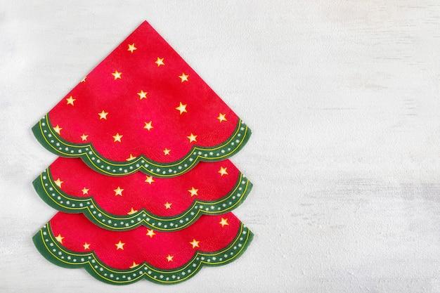 Alternativer weihnachtsbaum aus servietten. weihnachtszusammensetzung auf einem hellen hölzernen bedeckt im weißen schnee. copyspace
