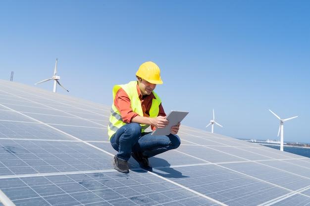Alternatives energiekonzept - ingenieur sitzt auf sonnenkollektoren, grüne energie und umweltfreundliches industriekonzept
