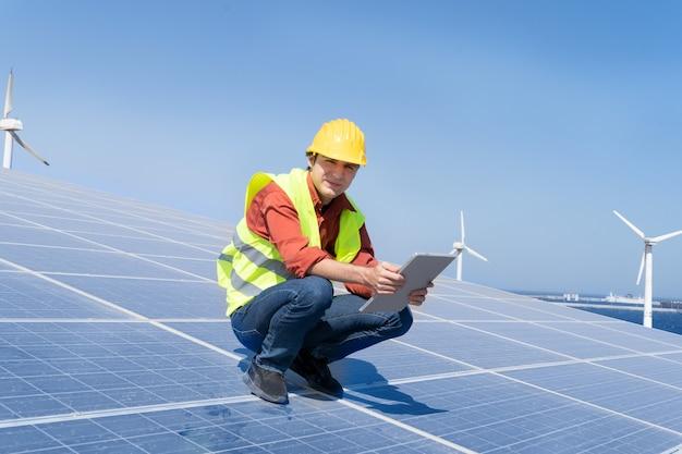 Alternatives energiekonzept - ingenieur sitzt auf sonnenkollektoren, grüner energie und umweltfreundlichem industriekonzept