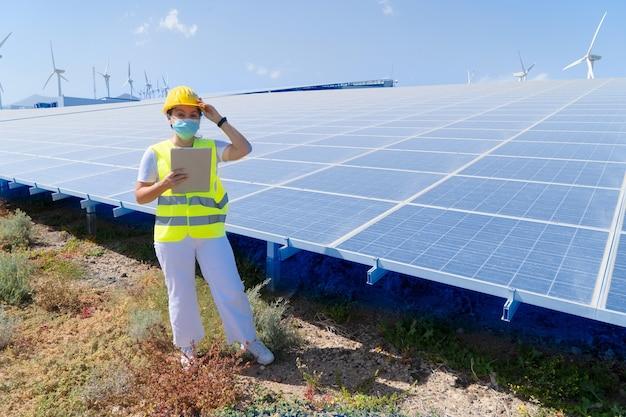 Alternatives energiekonzept - ingenieurfrau in der covid-maske, die vor sonnenkollektoren steht