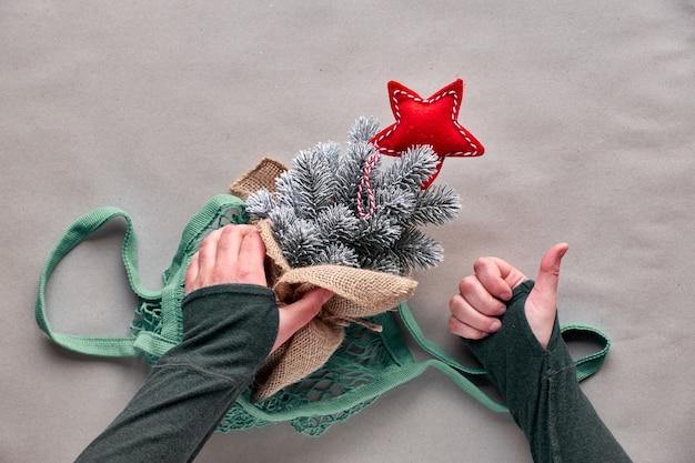 Alternatives grünes weihnachten, neujahrskonzept. flache lage, draufsicht auf bastelpapier. feiern sie mit einem falschen baum, ohne einen echten baum zu töten! plastikweihnachtsbaum mit rotem stern im stringbeutel, hand zeigen ok-zeichen.