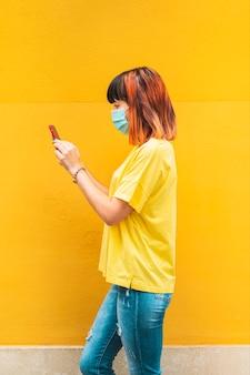 Alternatives kaukasisches modell mit dem seitlichen gehen des orangefarbenen haares, das das handy betrachtet und maske trägt