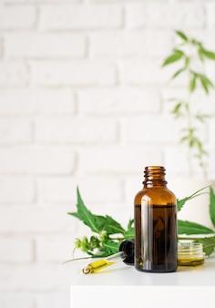 Alternativmedizin, naturkosmetik. cbd-öl und cannabis hinterlässt kosmetika-vorderansicht, kopierraum, mock-up-design