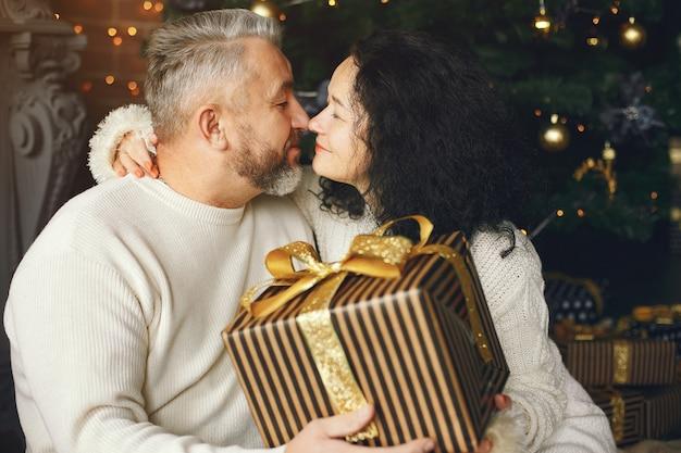 Alters- und personenkonzept. älteres paar mit geschenkbox über lichthintergrund. frau in einem weißen strickpullover.