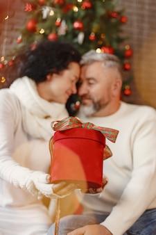 Alters- und personenkonzept. älteres paar zu hause. frau in einem weißen strickpullover.