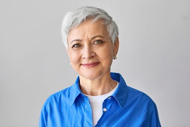 Alters- und schönheitskonzept. charmante positive reife europäische frau mit kurzen grauen haaren und falten, die isoliertes, selbstbewusstes lächeln darstellen und stilvolles blaues hemd tragen.