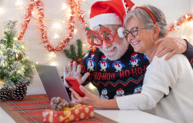 Altes älteres paar, das glücklich im videoanruf mit der familie in der weihnachtszeit lächelt. schöne ältere kaukasische familie, die neues jahr feiert