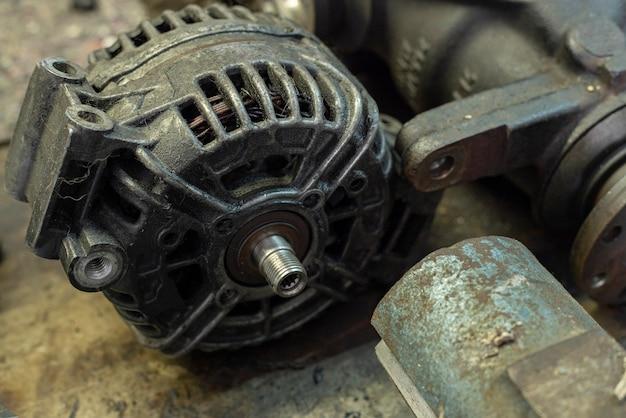 Altes auto-generator-detail in einer werkstattbank