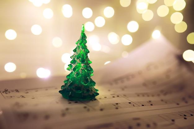 Altes blatt mit weihnachtsmusiknoten als hintergrund gegen unscharfe lichter. weihnachtsmusikkonzept