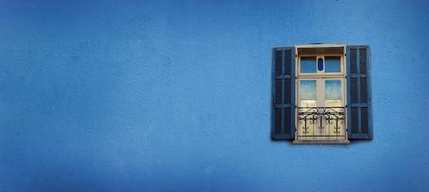 Altes blau gemalte fenster auf betonmauer. banner mit textfreiraum. pop-art-konzept, griechisches artfenster