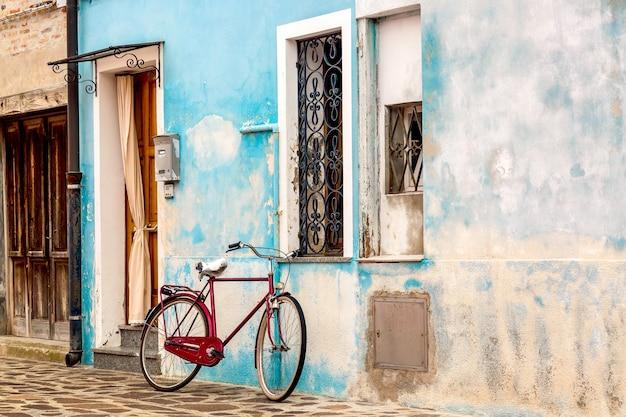 Altes blaues haus mit einem fahrrad in burano, venedig.
