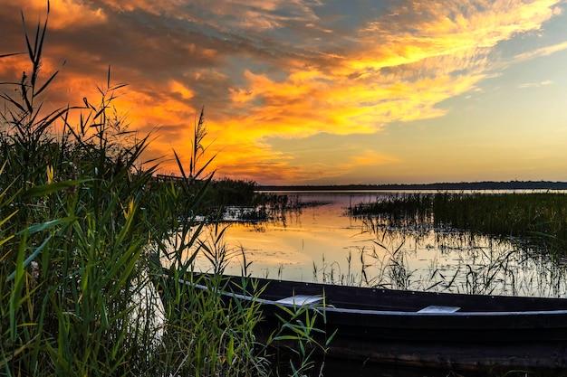 Altes boot angedockt an einem see während des goldenen sonnenuntergangs.