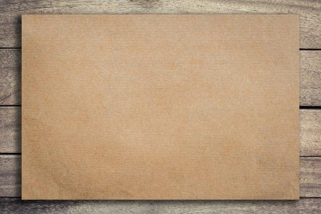 Altes braunes papier auf grunge hölzernem hintergrund und beschaffenheit mit raum.