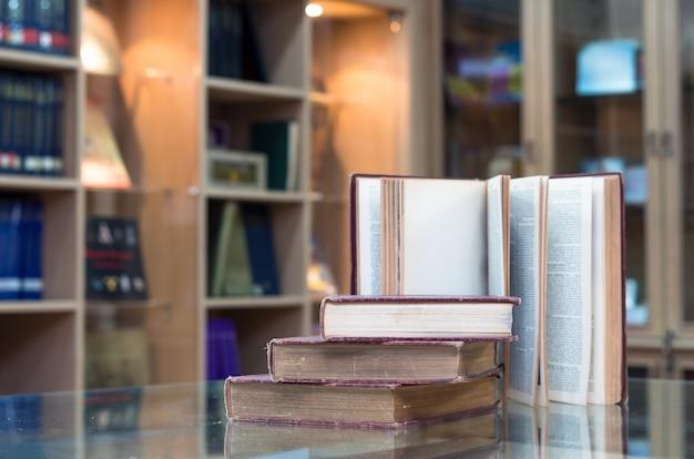 Altes buch auf dem glas schreibtisch in der bibliothek