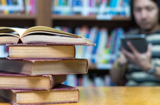 Altes buch auf dem schreibtisch in der bibliothek mit dem mann, der den buchhintergrund liest