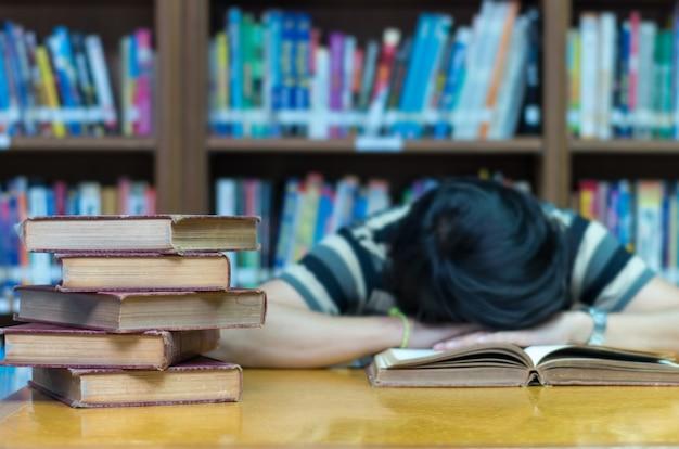 Altes buch auf dem schreibtisch in der bibliothek mit dem mann, der über dem buchhintergrund schläft
