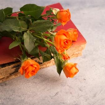 Altes buch und blumenblumenstrauß auf schäbiger oberfläche