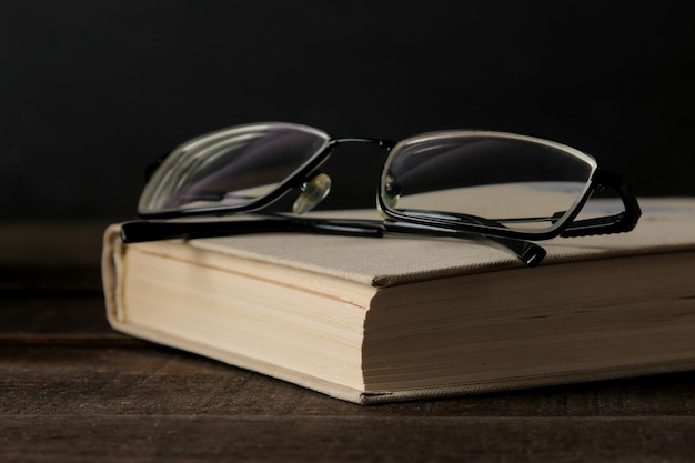 Altes buch und gläser auf einem braunen holztisch und auf schwarzem hintergrund. alte bücher. ausbildung. schule. lernen