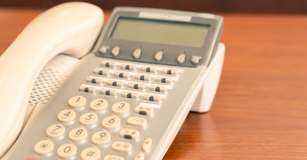 Altes bürotelefon der nahaufnahme auf dem schreibtisch für retro- innenraum der geschäftskommunikation