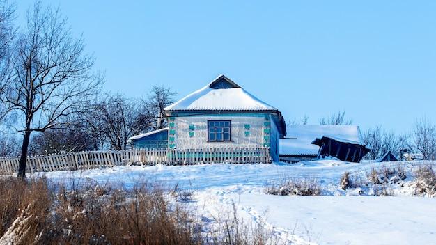 Altes dorfhaus im winter bei sonnigem wetter. das dorf im winter