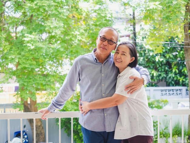 Altes ehepaar auf dem balkon umarmt