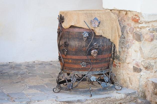 Altes eichenweinfaß mit eisenringen und -traube auf alter steinwand.